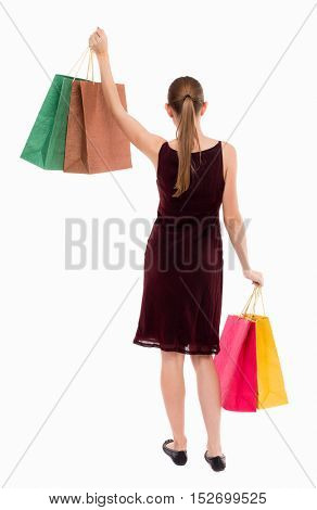 back view of woman with shopping bags . beautiful brunette girl in motion.  backside view of person.   Isolated over white background. A girl in a burgundy dress lifted in hand with shopping bags.