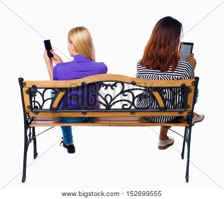 back view of two women sitting on bench and looks at the screen of the tablet.  Rear view people collection.   Isolated over white background. A couple of girls photographed using selfie stick.