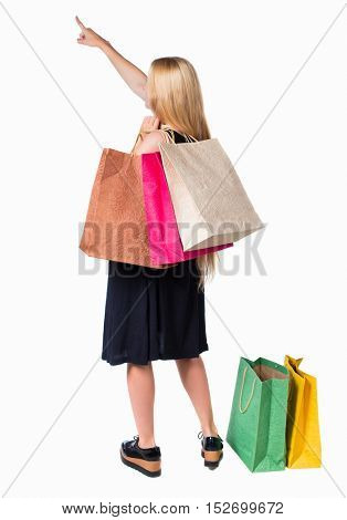 back view of woman  with shopping bags pointing . beautiful blonde girl in dress in motion. Isolated over white background. Long-haired blond girl holding shopping bags and showing a hand up