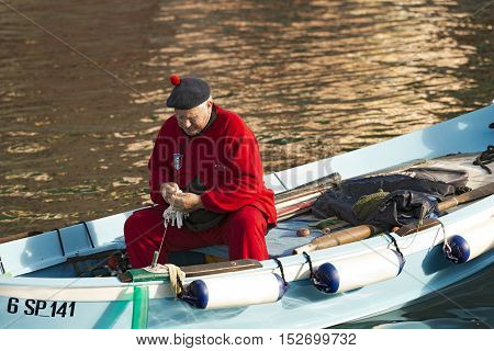 VERNAZZA LIGURIA ITALY - JANUARY 2 2015: An elderly fisherman in the port of Vernazza on a rowing boat. Cinque terre national park in Liguria Italy