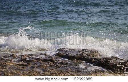Wave with splash and foam crest drops to seashore's stone. Clean blue water of tropical sea. A day at the beach. Rocks and stones near coastline. Oceanic landscape. Marine background photo