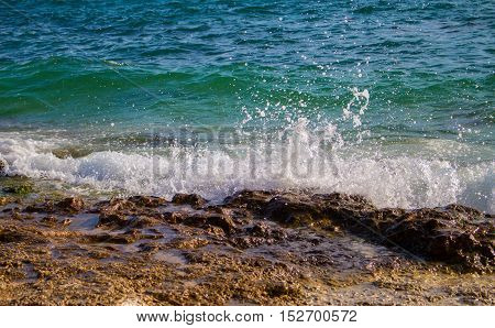 Wave with splash and foam crest drops to seashore's stone. Turquoise water of tropical sea. A day at the beach. Rocks and stones near coastline. Oceanic landscape. Marine background photo