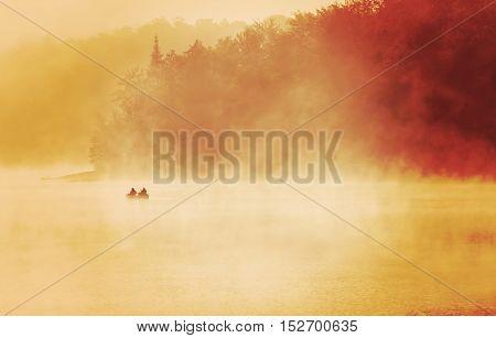 Exuding fishermen fishing in a lake, early misty foggy morning dramatic sunlight
