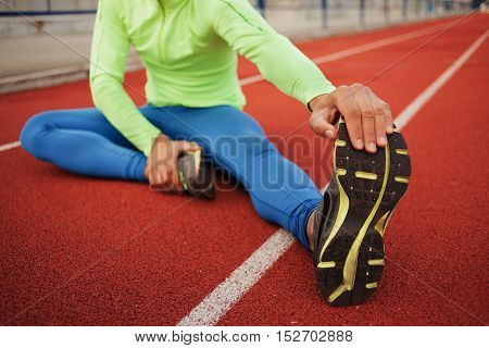 African runner stretching before workout. The guy preparing for training