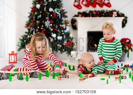 Happy little children in matching pajamas playing with Christmas presents - wooden toy railroad and car. Family Xmas morning in decorated living room with kids gifts fireplace and Christmas tree.