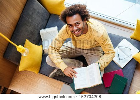 Top view of happy african american young man reading book and learning at home