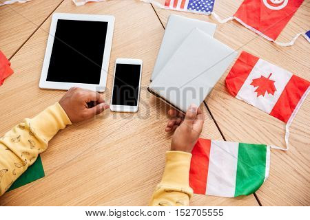 Top view of man holding book at the table with blank screen smartphone, tablet and flags of countries