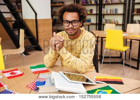Happy african young man in glasses studying using flags of countries and tablet with earphones in library