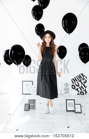 Full length of cheerful young woman standing and holding black balloons over white background