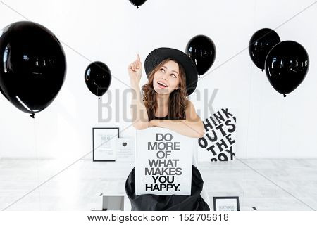 Smiling young woman in hat holding white board and pointing up over background with black balloons
