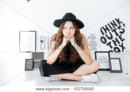 Sad frowning young woman sitting with legs crossed and thinking over white background with posters