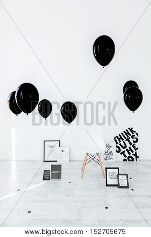Chair, posters with text and black air balloons over white background
