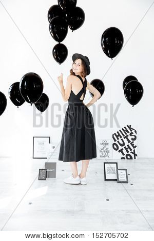 Smiling attractive young woman holding black balloons and looking back over white background