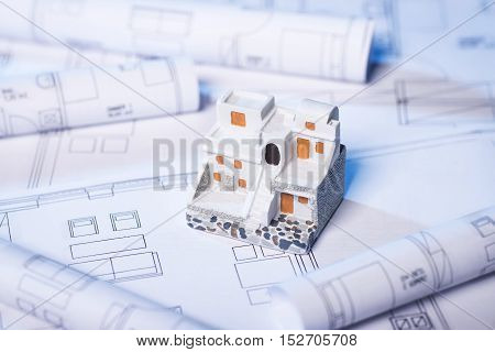 Blueprints and model house in classical Greek style