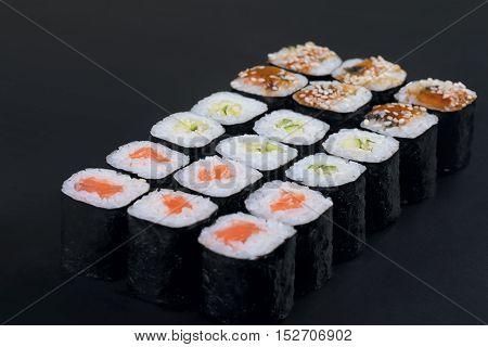Large nori rolls set on black background