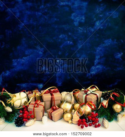 Christmas or New Year background: fur-tree, branches, gifts, colored glass balls, decoration and cones on a white, blue  background