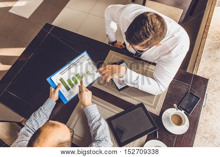 Two business people at a meeting in a cafe. Selective focus on papers graph.