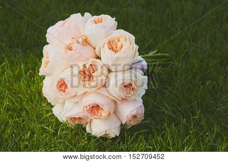 wedding bouquet of the bride- colorful wedding flowers at the grass. Elegant and classic bridal decoration roses. Retro style