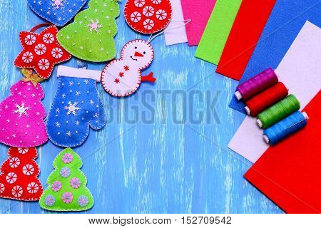 Felt Christmas decorations. Christmas tree, heart, star, ball, mitten, snowman diy, sewing kit, colorful felt sheets on blue wooden background. Simple sewing crafts