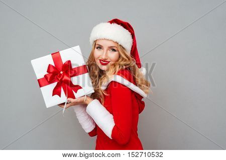 Smiling cute girl in red christmas outfit holding big gift box isolated on the gray background
