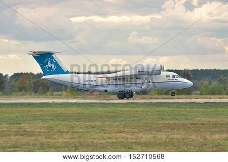 Kiev Region Ukraine - October 3 2010: Antonov An-74 cargo plane is taking off on stormy sunset - side view