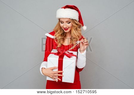 Beautiful blonde woman in red xmas outfit opening her present isolated on the gray background