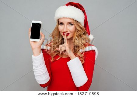 Attractive blond woman in santa claus dress and red hat holding blank screen mobile phone and showing silence gesture isolated on the gray background