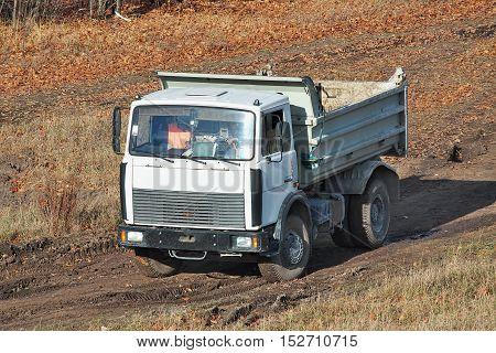 Kiev Ukraine - November 23 2010: Dump truck is driving along the muddy road