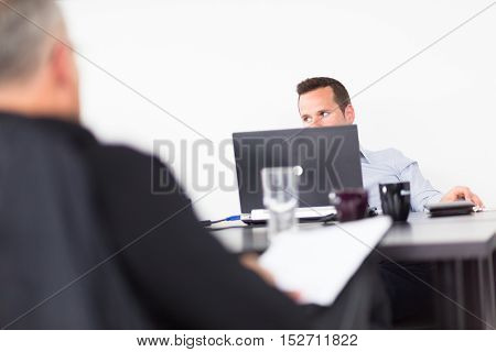 Workplace in modern office with businessman working on laptop during the meeting.