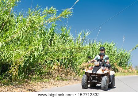 Woman with kid riding quad-bike, toned image