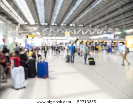 Blur background of airport hall with many suitcase and people
