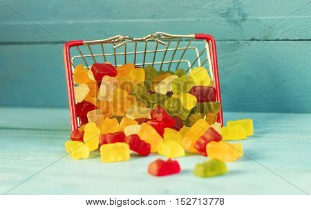 Shopping cart full of candies on the wooden background