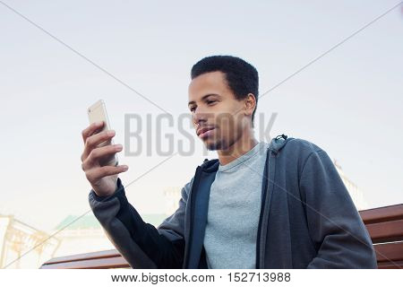 Handsome young Afro American man in sport wear is using smartphone, guy outdoors
