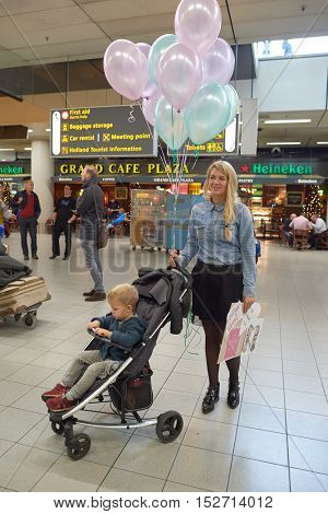 AMSTERDAM, NETHERLANDS - CIRCA NOVEMBER, 2015: woman with child at Amsterdam Airport. Amsterdam Airport Schiphol is the main international airport of the Netherlands.