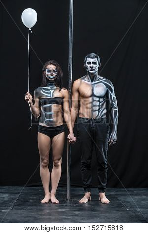 Amazing couple of pole dancers holds their hands together next to a pylon on a dark background in the studio. They have body-art. Girl wears black underwear and holds balloon. Guy wears black pants.
