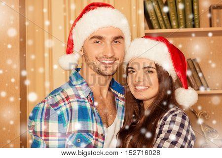Portrait Of Young Happy Family In Santa Hats Celebrating Xmas