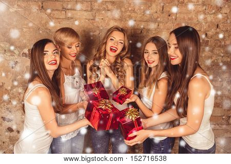 Cheerful Pretty Girls Giving Presents To Their Friend On New Year