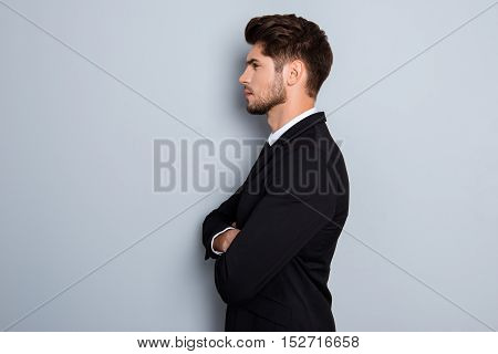 Side View Of Serious Businessman With Crossed Hands On Gray Background