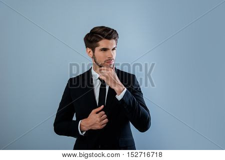 Minded Young Businessman In Black Suit Touching His Face