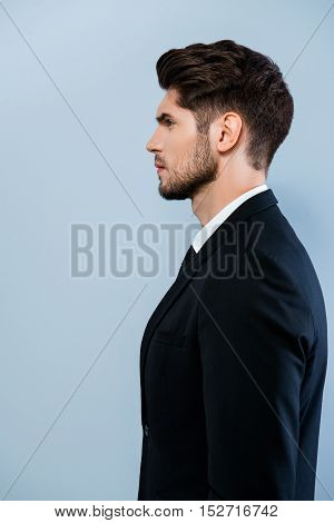 Side View Of Confident Serious Man In Black Suit