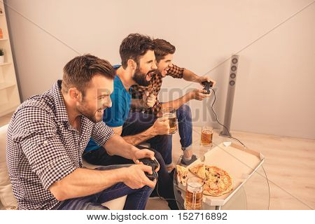 Three Excited Happy  Men Play Video Game With Beer And Pizza