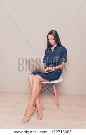 Young Pretty Businesswoman Sitting On Chair And Typing On Laptop