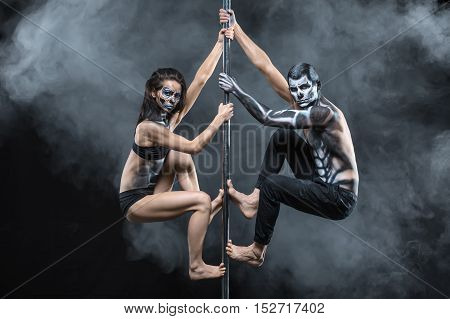 Delightful couple of pole dancers with a horrific body-art in the dark studio with a cloud of a smoke. They are hanging on a pylon and looking into the camera. Guy and the girl wear black sportswear.