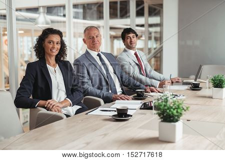 Portrait of a diverse group of smiling businesspeople sitting in a row together at a table in an office boardroom
