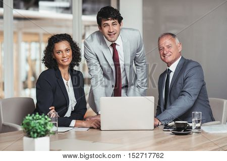 Portrait of three diverse businesspeople working together over a laptop at a table in an office boardroom