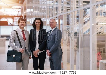 Portrait of a diverse group of smiling business colleagues standing together in the lobby of a modern office building