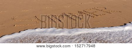 Summer word written in the sandy beach