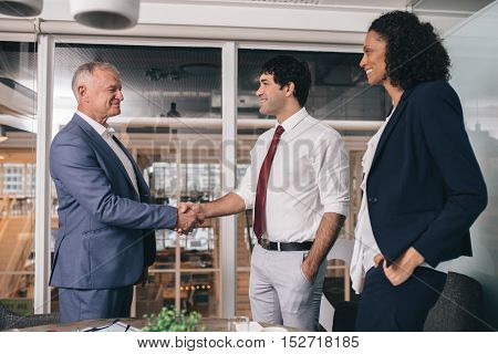 Mature manager shaking hands with a young staff member while standing in an office boardroom with a colleague looking on