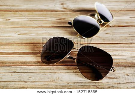 two unisex sunglasses close-up on a wooden background top view horizontal