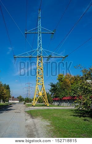 high voltage pole yellow blue against the blue sky